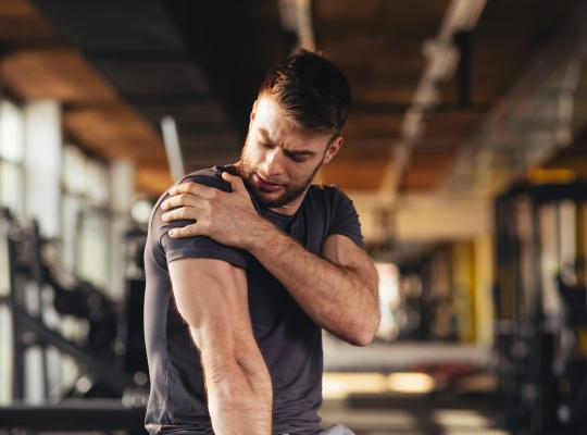 man in the gym looking at his injured shoulder