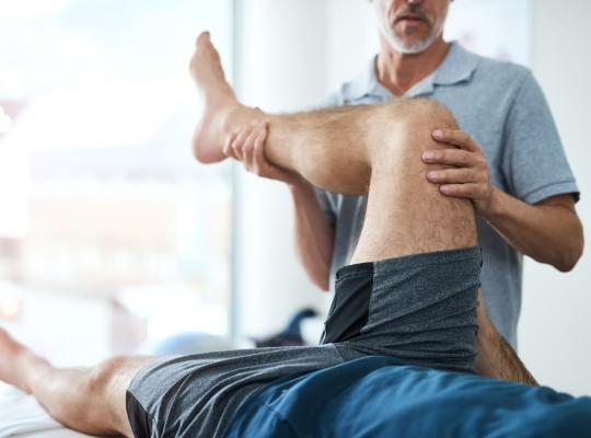 physical therapist moving patients knee