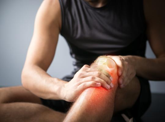 man rubbing painful knee joint