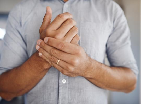 man holding wrist in pain while at home