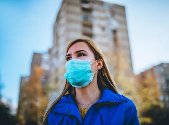 woman wearing surgical mask while walking in public area