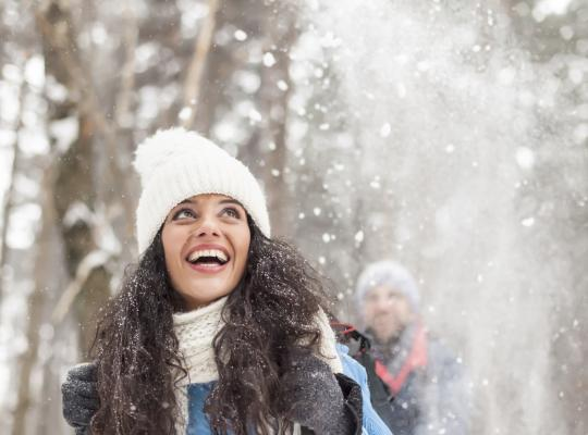 Cheerful young woman having fun in the snow forest stock photo