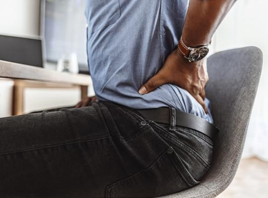 Man with back pain sitting in chair touching low back